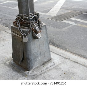 Heavy metal chains and padlocks wound around the base of a streetlight at the edge of a sidewalk