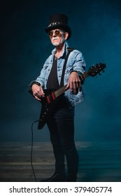 Heavy metal senior man with electric flying-v guitar in front of dark blue background.