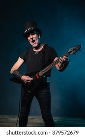 Heavy metal senior man with electric guitar in front of dark blue background.