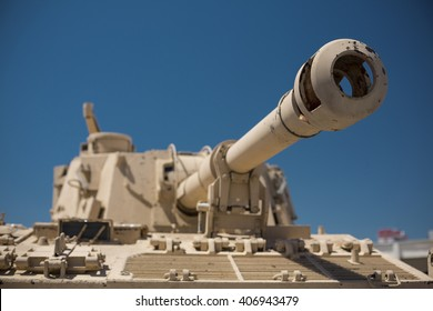 Heavy military tank vehicle desert camouflage army turret gun aiming on a target and ready to fire. The rotating turret barrel tip of a tank.