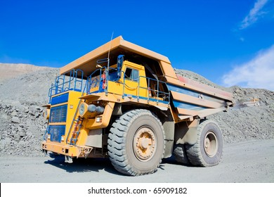 Heavy mining dump truck driving along the opencast