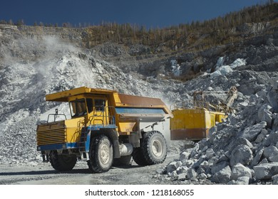 Heavy mining dump truck inside a limestone quarry, close-up. Heavy mining equipment.