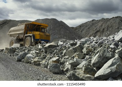 Heavy mining dump truck in a limestone quarry with huge fragments of rock in the foreground. Quarry equipment. Mining industry.