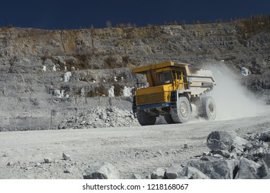 Heavy mining dump truck transports stone ore in a quarry for the extraction of limestone. Heavy mining equipment.