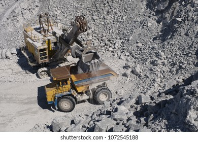 Heavy mining excavator loads rock ore into a heavy dump truck in a limestone quarry, close-up, top view. Heavy equipment. Mining industry.