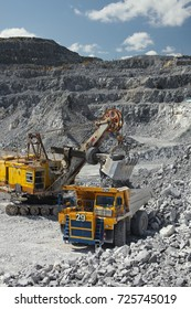 Heavy mining excavator loads rock ore into a dump-body large mining truck. Quarry equipment. Mining industry.