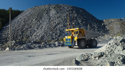 Heavy mining truck moves at high speed along the road in a stone quarry, distinct object on a blurry background, panorama. Mining industry.