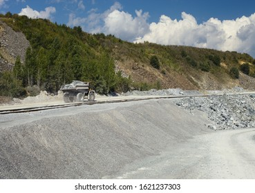 Heavy mining truck transports stone ore against a background of a panorama of a stone quarry.