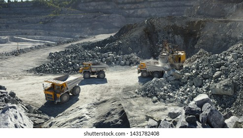 Heavy mining trucks near the excavator awaiting their turn to stone ore loading in limestone quarry, industrial panorama.