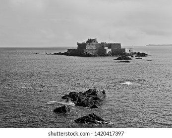Heavy mist begins to shroud Fort National on its tiny island off St Malo. Black and white image