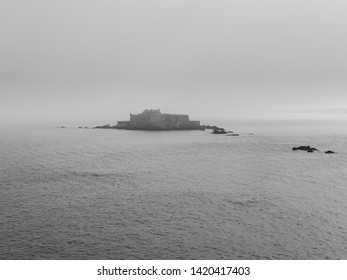 A heavy mist partially obscures the ancient Fort National in St Malo. Black and White image.
