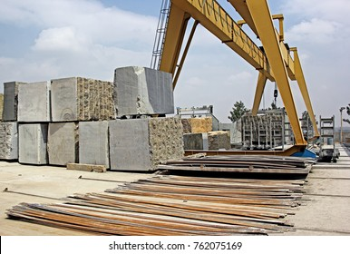 Heavy natural granite stone blocks stacked for processing into floor and wall tiles and slabs by cutting and polishing with the help of gantry crane and other heavy equipment.