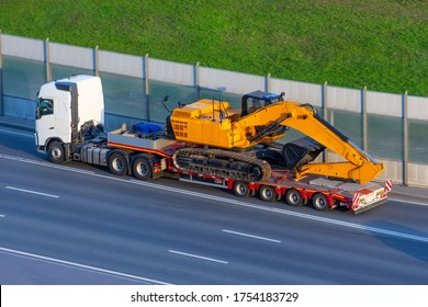 Heavy new yellow excavator on transportation truck with long trailer platform on the highway in the city