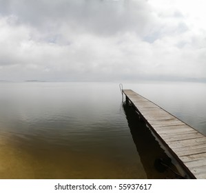 heavy overcast sky over empty pier on misty river Danube