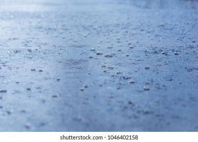 Heavy rain dripping into water making splashes. Blue natural background.