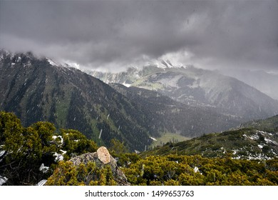 Heavy rain at mountains with dark clouds and snowy peak