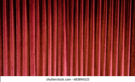 Heavy red velvet curtain in old fashioned theatre