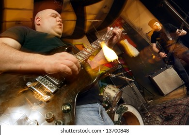 Heavy rock band playing. Shot with strobes and slow shutter speed to create lighting atmosphere and blur effects.