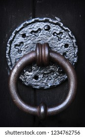 Heavy round iron knocker, a little aged and rusted, set upon a patterned plate into a sturdy old wooden door