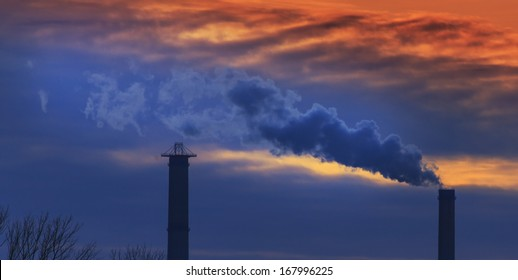 Heavy smoke spewed from coal powered plant smoke stacks under dramatic sunset
