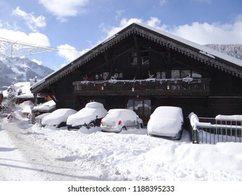 Heavy snow covers cars in a small hotel in Chatel, France