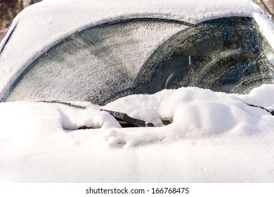 Heavy snow fallen on the windshield of a car during winter time