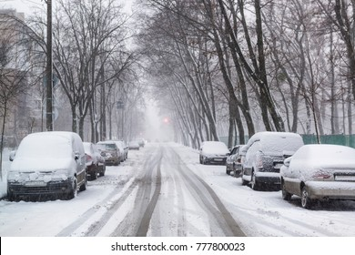 Heavy snowfall on the city streets in winter. Cars are covered by snow, slippery road