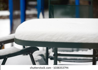 Heavy snowfall on a garden table and chairs