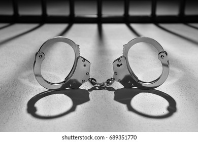 Heavy steel Handcuffs and on the background jail bars