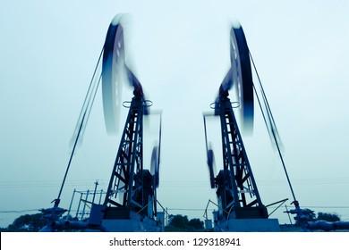 Heavy steel machines pumping oil.