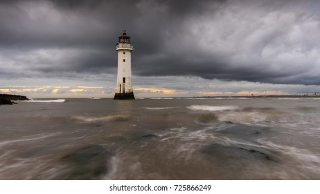Heavy storm clouds lie over New Brighton Lighthouse in Birkenhead, with water swirling over the rocks as the tide rushes over them.