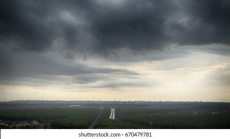 Heavy storm sky hangs over the Kiev city with a highway in the middle of the forest