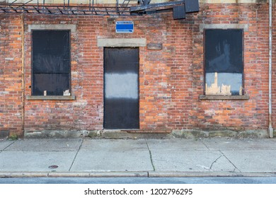 Heavy texture on brick building with boarded up windows