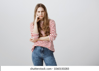 Heavy thoughts fill her mind. Bothered gloomy european female frowning being perplexed and frustrated, leaning head on fist, thinking or sulking from offence or insult, heaving bad day over gray wall