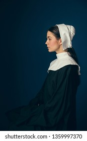Heavy thoughts. Medieval young woman as a nun in vintage clothing and white mutch sitting on the chair on dark blue background. Concept of comparison of eras. Vintage portrait.