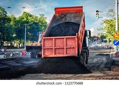 Heavy tipper unloads fresh hot smoking asphalt mix on a prepared surface for paving. Building and reconstruction roadway in the city. Modernization of urban infrastructure.