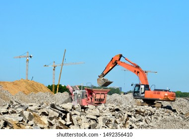 Heavy tracked excavator load stone, old asphalt or concrete waste into a mobile jaw crusher machine. Crushing and processing into gravel for recycling in concrete or cement production.
