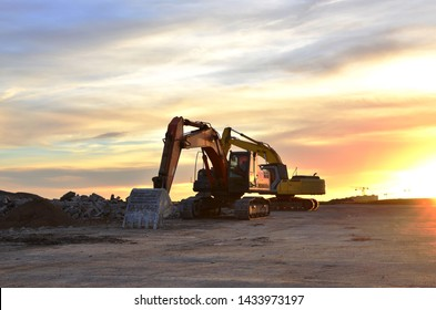 Heavy tracked excavators at a construction site on a background  sunset. Special heavy construction equipment for road construction - Image