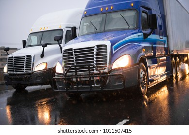 Heavy traffic with big rig semi trucks convoy going side by side with semi trailers transporting commercial cargo on highway in rain evening with headlight reflection on wet surface