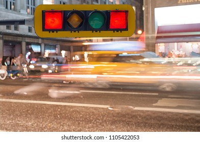 Heavy traffic with blurred lights through city street at night with red light right in front