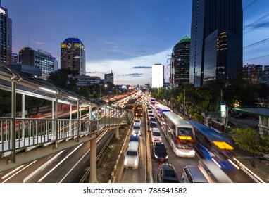 Heavy traffic during the rush hour on the highway in Jakarta business district at night in Indonesia capital city. The Transjakarta bus system has its own traffic lane to beat the congestion.