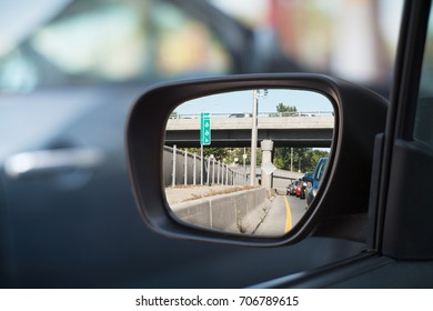Heavy traffic jam on highway viewed through the car rear mirror