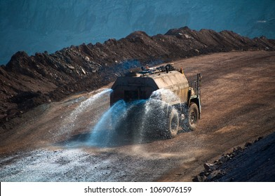 Heavy truck pours the road with water in the iron ore quarry. Dust removal, protection of the environment. Irrigation of the road from dust