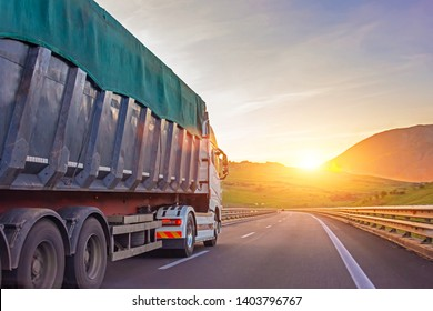 Heavy truck with a trailer for cargo, goods rides on a mountain highway, against the background of the evening sky a bright sunset. The concept of freight road transport