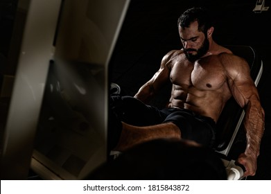 heavy weight workout of bearded strong man in fitness equipment during leg press training