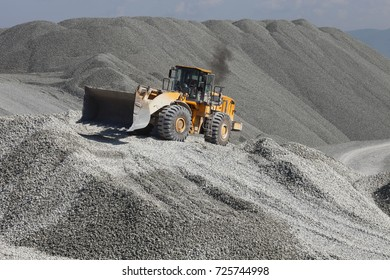 Heavy wheel loader excavator against the background of gravel hills. Quarry equipment. Mining industry.