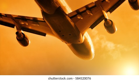Heavy widebody jet engine passenger airplane taking off against sunset sky with setting sun light aviation transportation theme aerial panoramic background silhouette isolated
