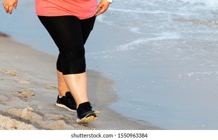 A heavy women from  the waist down is walking on the beach next to the water for exercise wearing spandex and running shoes.