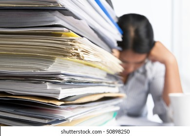 Heavy workload concept with pile of paper and woman on background. Selective focus
