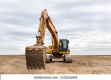 heavy yellow excavator with backhoe parked on construction site against dramatic sky